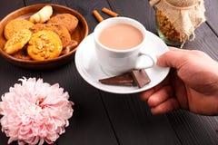En man rymmer en kopp kaffe och mjölkar Bredvid plattan är kakor och en rosa blomma inomhus ovanför sikt arkivbilder