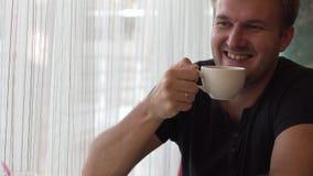 En man rymmer en kopp med en varm drink lager videofilmer
