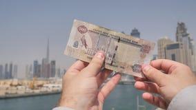 En man rymmer en sedel i händerna av 500 dirhams mot bakgrunden av staden av Dubai Enig arab för pengar stock video