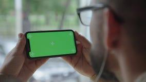 En man rymmer en smartphone med båda händer En stor bakgrundsbild arkivfilmer