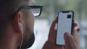 En man rymmer en smartphone nästan hans framsida och läser nyheterna eller en bok stock video