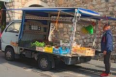 En man säljer grönsaker och frukter från en liten lastbil Arkivbild