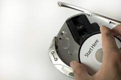 En man sätter in en CD i en cd spelare med ett meddelande för start här Arkivfoton
