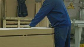 En man sågar trädörrmellanrum på maskinen, produktionen av byinredörrar stock video
