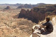 En man satt att se ut över bergen, Etiopien Arkivfoton