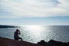 En man ser havet som sitter på en sten arkivbilder
