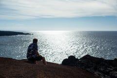 En man ser havet som sitter på en sten royaltyfri fotografi