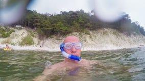 En man simmar i havet i exponeringsglas och med ett rör för att simma arkivfilmer