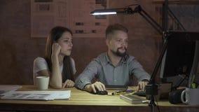 En man sitter framme av datoren och berättar flickan om arbete, visar ett finger till bildskärmen stock video