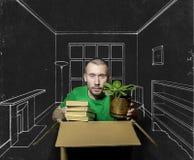 En man sitter i en åtsittande ask och rymmer i hans händer böckerna Arkivbilder