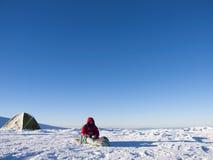 En man sitter i en sovsäck nära tältet fotografering för bildbyråer