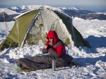 En man sitter i en sovsäck nära tältet royaltyfri fotografi