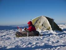 En man sitter i en sovsäck nära tältet och snöskorna fotografering för bildbyråer