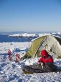 En man sitter i en sovsäck nära tältet och snöskorna royaltyfri bild