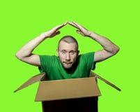 En man sitter i en nära ask och vek hans armar över hans hea Arkivbild