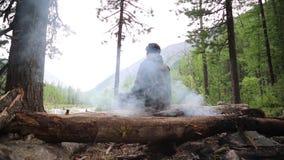 En man sitter nära en brand i skogen och ser in i avståndet arkivfilmer