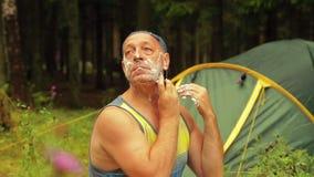 En man sitter nära ett turist- tält och rakar hans framsida stock video