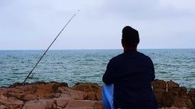 En man sitter och ser ut till havet stock video