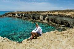 En man sitter på en avsats av vaggar ovanför havet på udde Greco Arkivbild