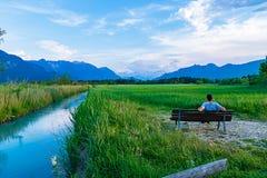En man sitter på en bänk i den Murnau heden och beundrar naturen arkivbilder