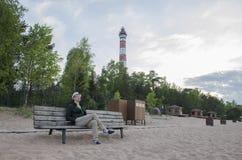 En man sitter på en bänk på en sandig strand royaltyfri fotografi