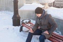 En man sitter på en bänk och att se telefonen Royaltyfri Fotografi