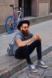En man sitter på ett moment med den enkla hastighetscykeln på bakgrund Fotografering för Bildbyråer