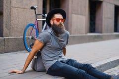 En man sitter på ett moment med den enkla hastighetscykeln på bakgrund Arkivbilder