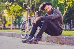 En man sitter på ett moment med den enkla hastighetscykeln på bakgrund Royaltyfri Fotografi