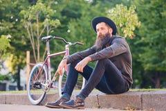 En man sitter på ett moment med den enkla hastighetscykeln på bakgrund Royaltyfri Bild