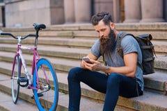 En man sitter på ett moment och att använda en smartphone Royaltyfri Fotografi