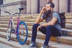 En man sitter på ett moment och att använda en smartphone Fotografering för Bildbyråer