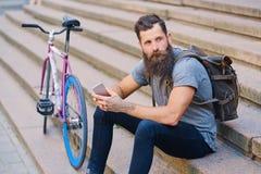 En man sitter på ett moment och att använda en smartphone Royaltyfri Bild
