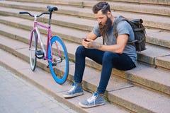 En man sitter på ett moment och att använda en smartphone Royaltyfria Bilder