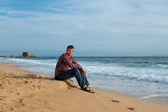 En man sitter på kusten av havet Arkivbild