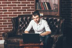 En man sitter på en lyxig soffa och arbetar bak en bärbar dator i hans kontor på bakgrunden av bokhyllan arkivbild
