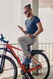 En man sitter på en röd bergcykel och rymmer en smartphone arkivfoto
