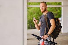 En man sitter på en röd bergcykel och rymmer en smartphone arkivbild
