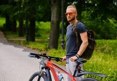 En man sitter på röd en utomhus- bergcykel arkivfoton