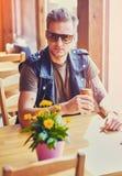 En man sitter på tabellen i ett kafé royaltyfri fotografi