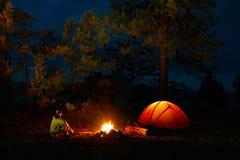 En man sitter vid branden nära ett tält på kusten av Lake Baikal Royaltyfria Bilder