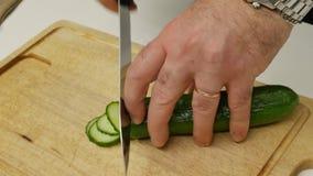 En man skivar gurkor för sallad Chefcook hugger av skivagurkan lager videofilmer