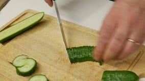 En man skivar gurkor för sallad Chefcook hugger av skivagurkan arkivfilmer