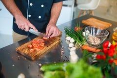 En man skivar tomater Närbild Begreppet av matlagning royaltyfri fotografi