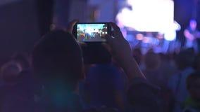 En man skjuter en nattkonsert på telefonen stock video