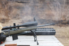En man skjuter ett gevär Plundra skytte med optisk sikt utomhus vid mannen Royaltyfri Foto