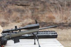 En man skjuter ett gevär Plundra skytte med optisk sikt utomhus vid mannen Arkivbilder