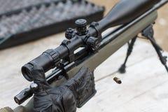 En man skjuter ett gevär Plundra skytte med optisk sikt utomhus vid mannen Arkivbild
