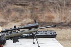 En man skjuter ett gevär Plundra skytte med optisk sikt utomhus vid mannen Royaltyfria Foton