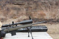En man skjuter ett gevär Plundra skytte med optisk sikt utomhus vid mannen Royaltyfria Bilder